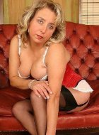 Mature in red corset poses and takes off stockings