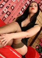 Sexual mature in nylon stripping on red sofa