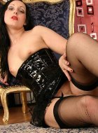 Brunette mature in nylons and latex corset posing