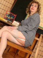 Mature teacher in stockings showing her legs
