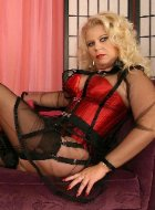 Blonde mature in stockings and red corset posing