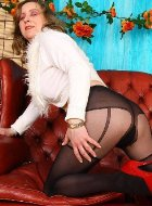 Hottest mature in pantyhose posing on red sofa
